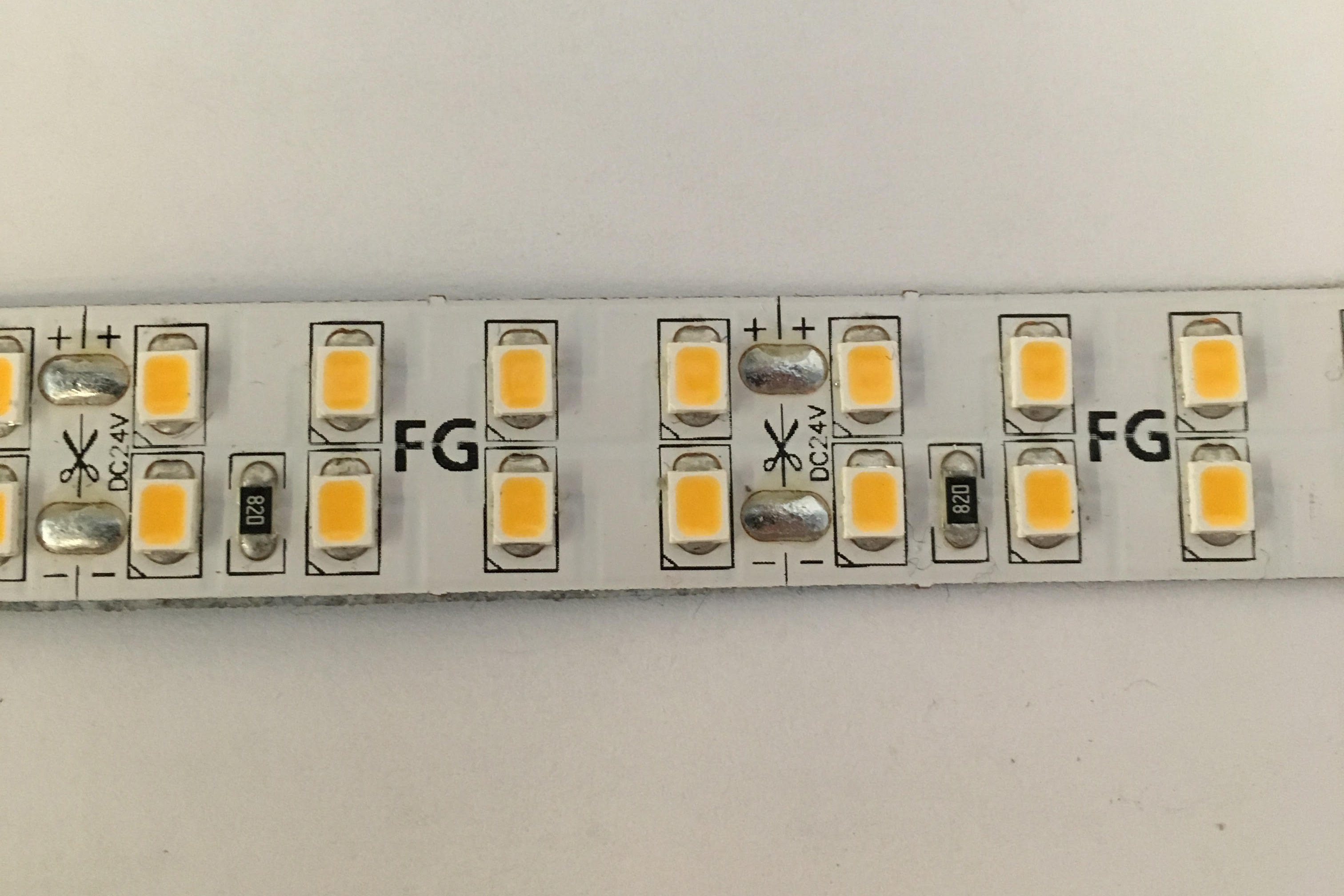 Close up on an LED diode strip. The individual LEDs appear as small orange and yellow rectangles across the white colored strip. Instructional text is printed on the strip, around the LED diodes indicating where they should be cut.