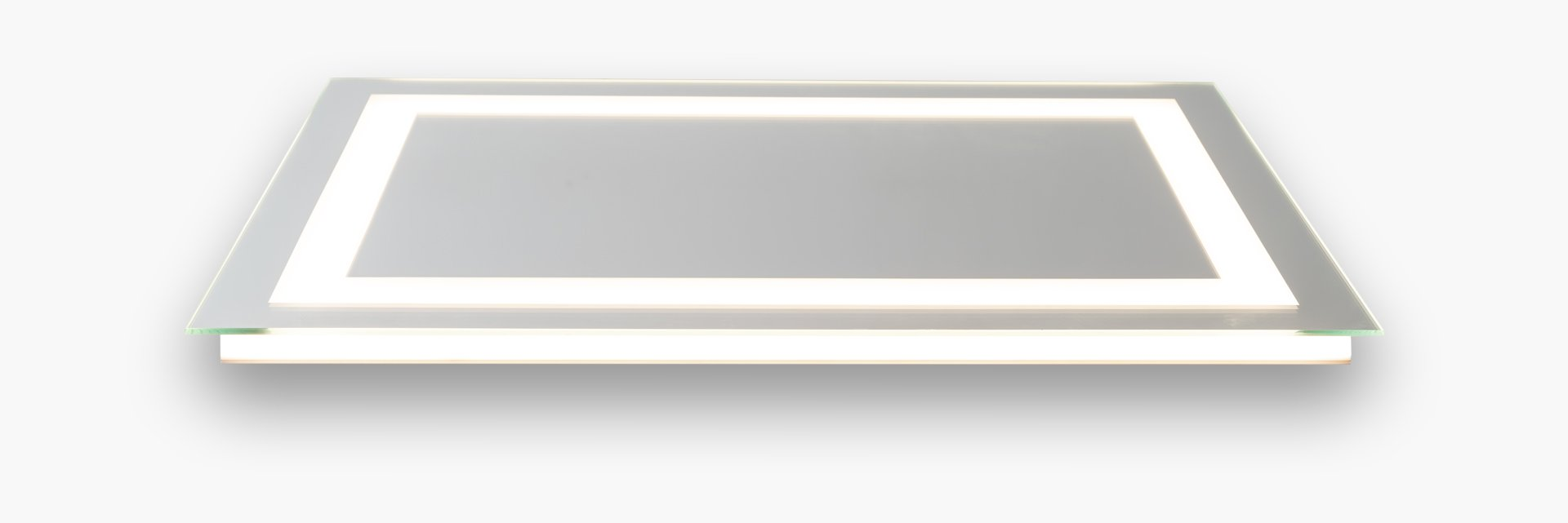 Side view of the Matrix Mirrors L1 model LED mirror. At this angle, the mirror is laid on its back - parallel to the ground. The direct LEDs are inset and on. The mirrors indirect backlight is also on.