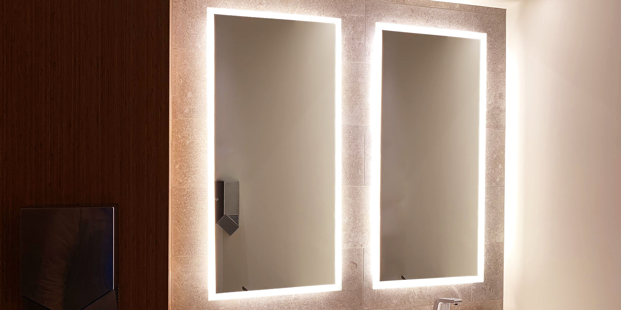 Matrix Mirrors L2 mirrors installed in a commercial bathroom setting. Full frame frost covers the diameter of the mirror. The frost is illuminated with LEDs. The mirrors shine on a bathroom with white walls on the right, a stone tile backsplash, and wood siding on the left.
