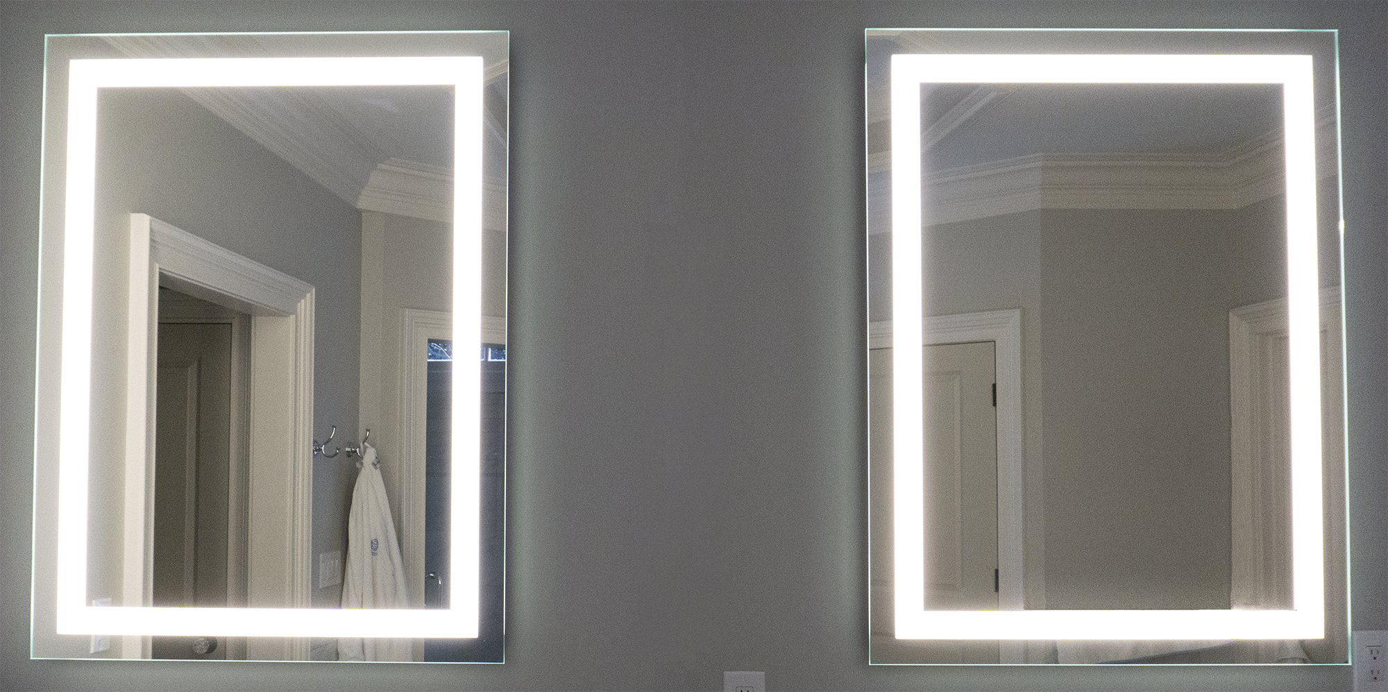 This image shows two Matrix Mirrors L1 model LED mirrors installed in a residential bathroom. The mirrors are direct lit only each having an inset frame of frost. The light shining from the mirrors is a clean, white light reflecting on white walls in the bathroom. A bath robe hangs in the reflection of the left mirror.
